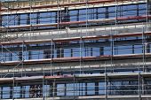 picture of scaffold  - Parts of a scaffolding in front of a glass facade - JPG