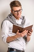stock photo of casual wear  - Handsome smiling man in casual wear reading the book on grey background - JPG