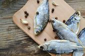 image of cod  - Salty stockfish cod on wooden board with gaarlic and pepper - JPG