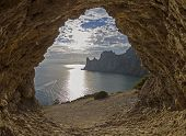 picture of grotto  - View of the sunny lane and the coastal cliffs from a small rocky grotto - JPG