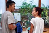 stock photo of pyjama  - young woman washing dirty dishes while husband dry off in kitchen - JPG