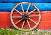 foto of wagon wheel  - wooden wheel of an old wagon on the background of a timbered wall - JPG