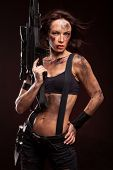 stock photo of sniper  - Sniper woman in leather sexy wear. Riot woman with gun on dark background