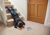 picture of concentration  - Child falling down the stairs whilst playing on digital tablet not concentrating concept for safety at home - JPG