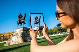 pic of albania  - Young woman tourist photographing with digital tablet Skanderbeg monument in Tirana - JPG