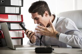 image of screaming  - Young Angry Businessman sitting in the office and screaming on the phone - JPG
