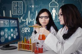 pic of chemical reaction  - Beautiful schoolgirls doing research and looking at the reaction of chemical liquid in the lab - JPG