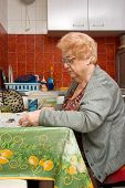 foto of elderly woman  - elderly woman in a small apartment kitchen reading her morning paper while she has her tea - JPG