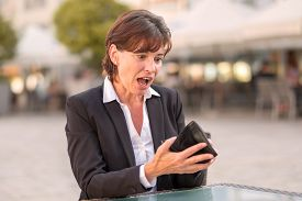 foto of horrifying  - Horrified woman unable to pay her bill at a street cafeteria as she realises that her wallet is empty and she does not have her credit card - JPG