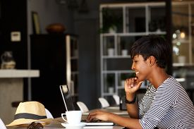 image of cafe  - Side portrait of a smiling young african american woman using laptop in cafe - JPG
