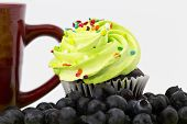 Red Mug And Cupcake With Green Frosting Surrounded By Blueberries_1627