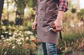 Selective Focus Of Gardener In Apron Holding Pruning Shears In Hand poster
