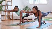 Young attractive couple practising yoga stretching workout at home, healthy lifestyle body care poster