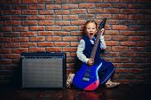 Modern little girl in school uniform posing with electric guitar over brick wall background. Rock st poster