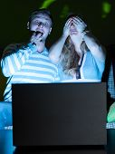 stock photo of computer-screen  - couple is watching scary movie indoors at night - JPG
