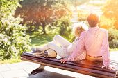 Middle-aged couple relaxing on park bench poster