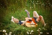 Teenage Boy Lying On Grass With His Acoustic Guitar poster