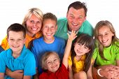 foto of happy family  - A happy family huddles close to each other posing for a family portrait - JPG