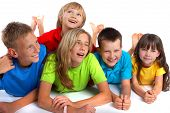 stock photo of happy kids  - A group of happy kids in bright shirts smiling and posing for the camera - JPG
