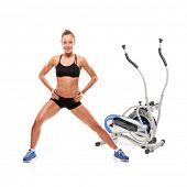 An athlete woman posing in front of a cross trainer machine isolated on white background