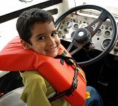 Little Boy Driving A Big Boat