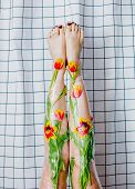 Woman Holds Her Legs Up Wrapped With Cellophane And Tulips Flowers. poster