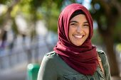 Portrait of young muslim woman wearing hijab head scarf in city while looking at camera. Closeup fac poster
