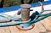 Gray Cleat With Blue Rope For Ships And Boats, Close Up. Gray Near The Pin For Ships And Boats In Th poster
