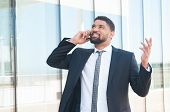 Cheerful Businessman Talking On Phone And Celebrating Good News And Success. Young Latin Man In Form poster