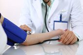 Unknown Doctor Woman Checking Blood Pressure Of Female Patient, Close-up. Cardiology In Medicine  An poster