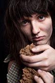 Retrato de una mendigo pobre mujer con un pedazo de pan en sus manos