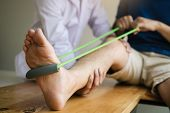 Patient Use Resistance Band Stretching Out His Leg With Physical Therapist Helps In Clinic Room. poster