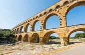 Pont du Gard is an old Roman aqueduct, southern France near Avignon. Reflection in the river Gard poster