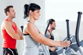 Gym fitness club indoor with young people training on treadmill and elliptical