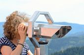 Woman Tourist Looking Through A Binocular Telescope From A Vantage Point In Mountainous Terrain poster