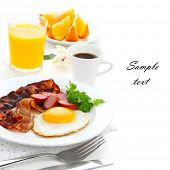Breakfast with bacon, fried egg and orange juice on white isolated background(With sample text)