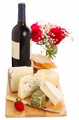 Different cheese with wine and roses isolated on white background