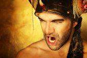 Sexy poderoso guerrero gritando contra fondo de oro
