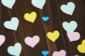 Many colorful paper hearts on wooden table close-up