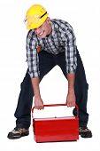laborer lifting heavy toolbox