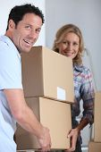 Couple moving pile of boxes