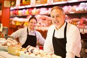 stock photo of salami  - People working in a grocery store - JPG