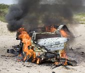 stock photo of blown-up  - Automobile that has just blown up that is in flames