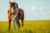 stock photo of cowgirl  - brunette cowgirl woman posing with horse outdoors portrait - JPG