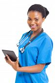 stock photo of scrubs  - beautiful female african american medical nurse with tablet computer on white - JPG