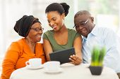 foto of granddaughters  - cheerful african family at home using tablet pc - JPG