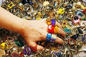 image of thrift store  - A woman tries on many rings from a huge vintage pile - JPG