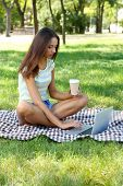 Beautiful young girl with laptop in park