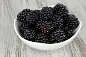 Sweet blackberries in bowl on table close-up