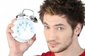 Young man with an alarm clock